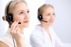 Ufficio luminoso della call center Due donne bionde in una cuffia avricolare Immagini Stock
