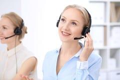 Ufficio luminoso della call center Due donne bionde in una cuffia avricolare Fotografie Stock