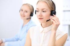 Ufficio luminoso della call center Due donne bionde in una cuffia avricolare Fotografia Stock Libera da Diritti