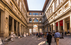 Uffizi Gallery in Florence Italy. Florence, Italy - Oct 5, 2016. Tourists browsing through The Uffizi Gallery museum in Florence, and walking toward the Arno Royalty Free Stock Images