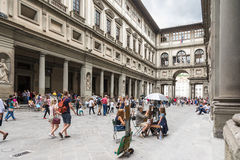 Uffizi museum. Florence, Italy – August 26,2014:Many tourists strolling in the Uffizi gallery in the middle of the street artist or to go to the museums during Royalty Free Stock Image