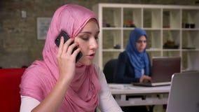 Ufna ładna muzułmańska dziewczyna skupia się mieć telefon rozmowę wszystko w jej umysłach, siedzi w ceglanym biurze z innym język
