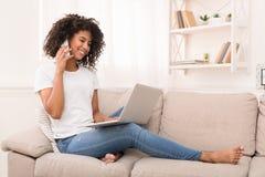Ufna afroamerykańska dziewczyna używa laptop i opowiadający na smartphone obrazy stock