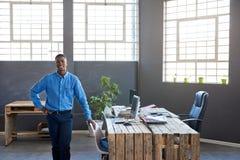 Ufna Afrykańska biznesmen pozycja przy jego biurkiem w biurze fotografia royalty free
