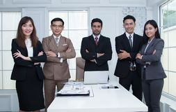 Ufna biznes drużyny pozycja i ono uśmiecha się w nowożytnym biurowym lo Fotografia Royalty Free