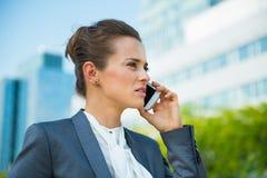 Ufna biznesowa kobieta opowiada smartphone w biurowym okręgu Zdjęcie Royalty Free