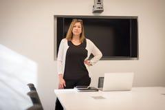 Ufna bizneswoman pozycja w sala konferencyjnej z laptopem obraz royalty free