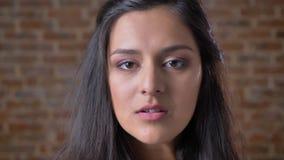 Ufna caucasian brunetki dziewczyna patrzeje kamerę, portret, ściana z cegieł w tle