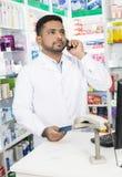 Ufna farmaceuta Używa telefon Podczas gdy Trzymający Kredytową kartę Fotografia Stock
