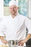 Ufna i uśmiechnięta szef kuchni pozycja w wielkiej kuchni Zdjęcia Royalty Free