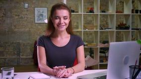 Ufna imbirowa kobieta siedzi prosto przy jej miejsce pracy i patrzeje kamerę z ładnym uśmiechem na ona miło
