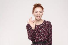 Ufna kobieta z powabnym uśmiechem robi ok gestowi jest ag Obraz Royalty Free