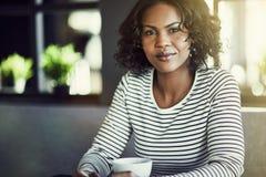 Ufna młoda Afrykańska kobieta pije kawę w kawiarni fotografia royalty free