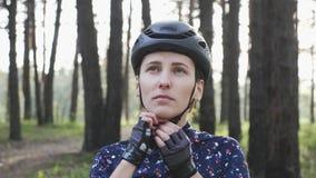 Ufna młoda cyklista kobieta patrzeje kamera stawia dalej hełm Triathlon poj?cie swobodny ruch zbiory wideo