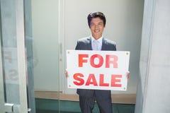 Ufna pośrednik w handlu nieruchomościami pozycja przy dzwi wejściowy pokazuje dla sprzedaż znaka Obrazy Stock