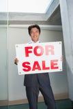 Ufna pośrednik w handlu nieruchomościami pozycja przy dzwi wejściowy pokazuje dla sprzedaż znaka Zdjęcie Stock