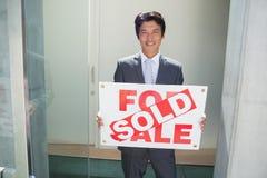 Ufna pośrednik w handlu nieruchomościami pozycja przy dzwi wejściowy seansem sprzedawał znaka Zdjęcie Stock
