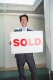 Ufna pośrednik w handlu nieruchomościami pozycja przy dzwi wejściowy seansem sprzedawał znaka Zdjęcie Royalty Free