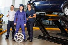 Ufni mechanicy Trzyma wyrwania Przy garażem zdjęcie royalty free