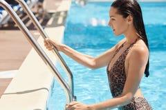 Ufni sporty charyzmatyczni wzorcowi macanie basenu schodki z jej rękami, wynikający wodę, wydaje jej wakacje z przyjemnością, obraz royalty free