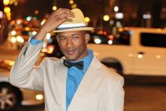 Ufny Afrykański mężczyzna mienia kapelusz Podczas gdy Chodzący miasto ulicy przy nocą Zdjęcia Royalty Free