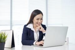 Ufny azjatykci bizneswomanu obsiadanie biurkiem z laptopem wewnątrz daleko obraz stock