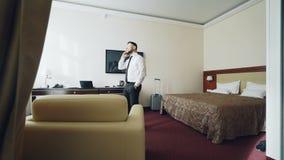 Ufny biznesmen opowiada na telefonie komórkowym podczas gdy chodzący wokoło pokoju hotelowego Podróż, biznes i ludzie pojęć, zdjęcie wideo