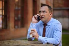 Ufny biznesmen opowiada na telefonie outdoors Zdjęcie Royalty Free