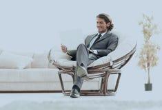 Ufny biznesmen pracuje z laptopu obsiadaniem w wygodnym karle Obraz Royalty Free