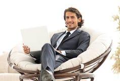 Ufny biznesmen pracuje z laptopu obsiadaniem w wygodnym karle Zdjęcia Stock