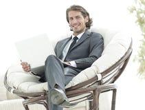 Ufny biznesmen pracuje z laptopu obsiadaniem w wygodnym karle Fotografia Stock