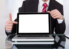 Ufny biznesmen wystawia laptop przy biurkiem Obraz Royalty Free