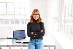 Ufny bizneswoman ono uśmiecha się ty i patrzeje kamerę podczas gdy stojący w biurze zdjęcie stock