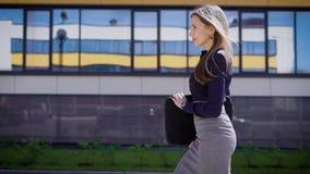 Ufny bizneswomanu odprowadzenie przy biurem Boczny widok ufny młody żeński przedsiębiorcy odprowadzenie przy budynkiem biurowym zdjęcie wideo