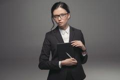Ufny brunetka bizneswoman trzyma dzienniczek w czarnych eyeglasses i kostiumu Zdjęcia Stock