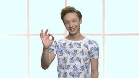 Ufny caucasian nastoletniego chłopaka seansu ok znak zdjęcie wideo