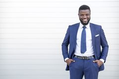 Ufny czarny biznesowy mężczyzna patrzeje kamerę z kopii przestrzenią w eleganckiej kostium pozycji przeciw ścianie zdjęcie stock