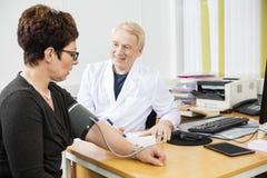 Ufny Doktorski Sprawdza pacjenta Żeński ciśnienie krwi obraz stock