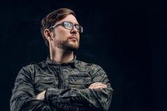 Ufny hacker w eleganckiej militarnej koszula pozuje z krzyżować rękami i patrzeje z ukosa fotografia royalty free