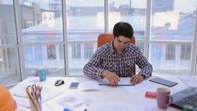Ufny i atrakcyjny biznesmen pracuje z rysunkami, projekty w świetle, nowożytny biuro pojęcia prowadzenia domu posiadanie klucza z zbiory wideo