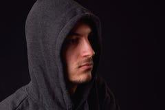 Ufny i poważny młody człowiek jest ubranym czarnego hoodie na czerni Fotografia Stock