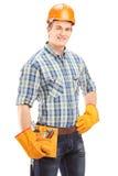 Ufny i uśmiechnięty ręczny pracownik patrzeje camer z hełmem Zdjęcia Stock