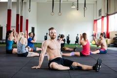 Ufny instruktora obsiadanie Podczas gdy klienci Ćwiczy W Gym Fotografia Royalty Free