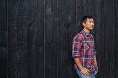 Ufny młody Azjatycki mężczyzna opiera przeciw ciemny ścienny outside zdjęcie royalty free