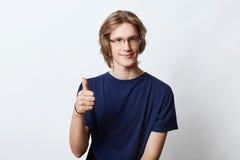 Ufny męski freelancer z eleganckim uczesaniem, będący ubranym widowisko, pokazuje ok znaka podczas gdy podnoszący jego kciuk, ono Obraz Royalty Free