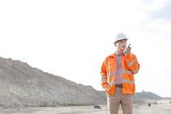 Ufny męski nadzorca używa talkie na budowie przeciw jasnemu niebu Zdjęcia Stock