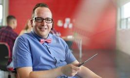 Ufny męski projektant pracuje na cyfrowej pastylce w czerwonej kreatywnie powierzchni biurowa Zdjęcia Stock
