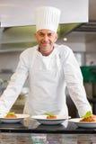 Ufny męski szef kuchni z gotującym jedzeniem w kuchni zdjęcia royalty free