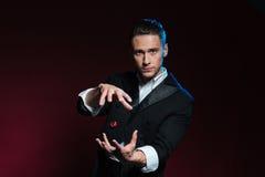 Ufny młodego człowieka magika seans kantuje używać jeden latania kostka do gry zdjęcie stock