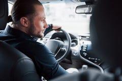Ufny młody biznesmena obsiadanie przy kołem jego nowy samochód obrazy royalty free